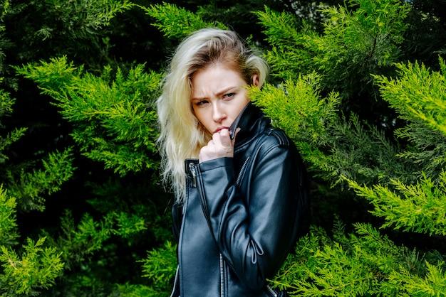 屋外に立っている黒い革のジャケットを着てモミの木の後ろに隠れている怒っている女性