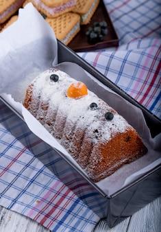 Вид сбоку торта с изюмом и сахарной пудрой на скатерть