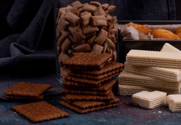 Вид сбоку шоколадное печенье и хрустящие вафли на темном