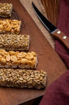Вид сбоку баров меда с арахисом и семечками на деревянной доске