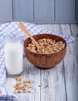 Вид сбоку воздушный сладкий рис в карамели в деревянной миске подается со стаканом молока на деревенском