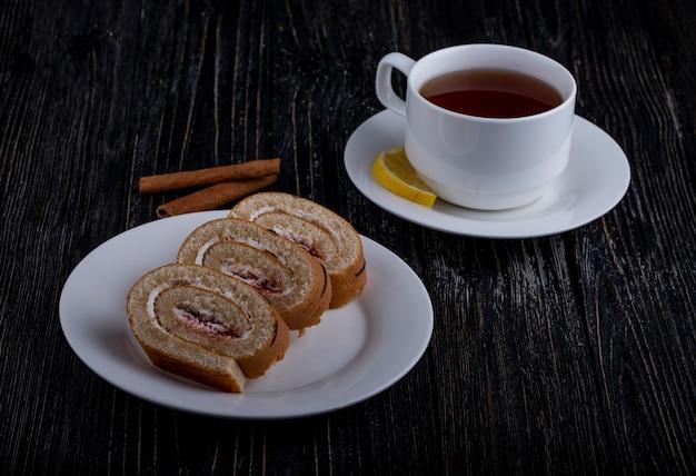 Вид сбоку ломтиков швейцарского рулета со взбитыми сливками и малиновым вареньем на тарелке с чашкой чая на деревенском