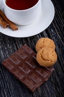 Вид сбоку темного шоколада с печеньем и чашкой чая на деревенском