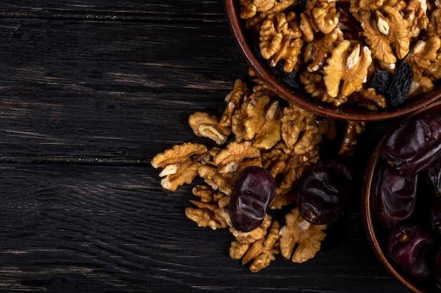 Вид сверху грецких орехов в миску и сладких сушеных фруктов на деревянных