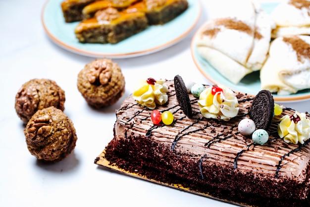チョコレートケーキにクリームとクッキーをトッピング