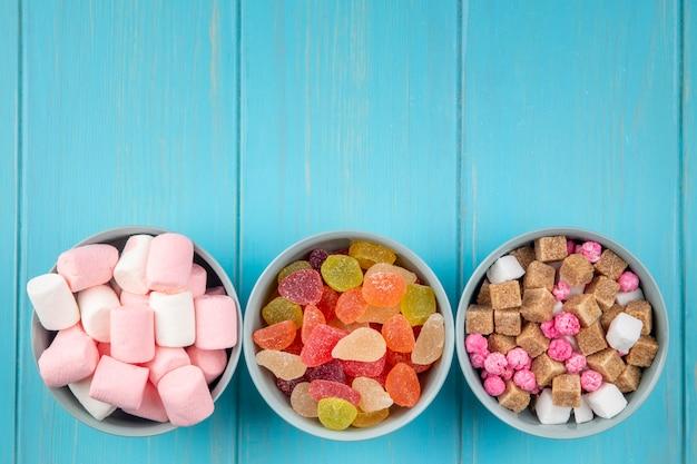 Вид сверху различных конфет красочные мармеладные конфеты зефир и кубики коричневого сахара в мисках на синем