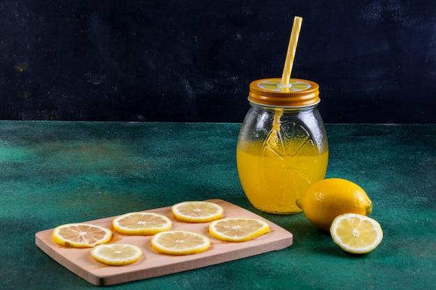 黒板のレモンとレモンスライスの瓶に正面レモネード