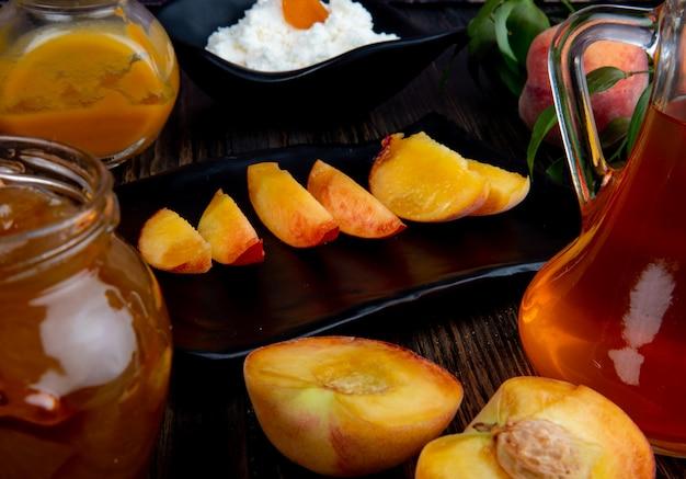 素朴な木製の背景にブラックトレイと桃のジャムとガラスの瓶にスライスした桃の側面図