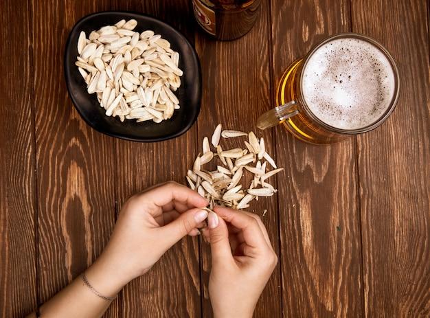 Женщина ест соленые закуски семена подсолнечника с кружкой пива на деревенском деревянный вид сверху