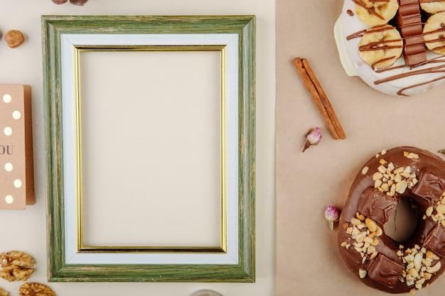 Взгляд конца-вверх рамки с печеньями и циннамоном и грецкими орехами на белизне с космосом экземпляра
