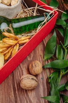 Вид сбоку бутылки пива с мини-крендели и соломы в красной коробке и грецкие орехи на деревенском