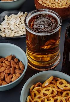 Вид сбоку на кружку пива с закусками, арахисом, семечками миндаля и мини кренделями на черном