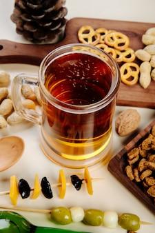 Вид сбоку на кружку пива с различными солеными закусками на столе