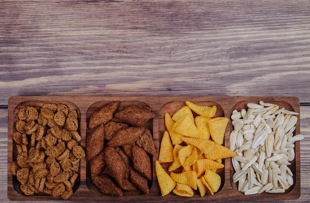 Вид сбоку разнообразных закусок к пиву сухарики чипсы и семена подсолнечника на деревянной тарелке на деревенском с копией пространства