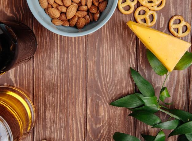 Вид сверху закуски к пиву миндаль в миске мини крендельки с кусочком сыра с кружкой пива на деревенском дереве с копией пространства