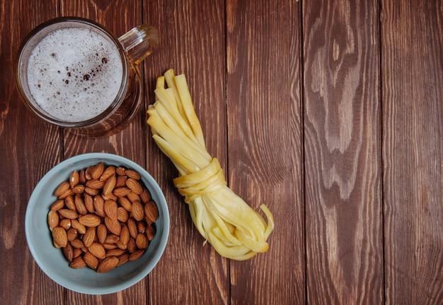 Вид сверху закуски к пиву миндаль в миску и сыр строки с кружкой пива на деревенском дереве с копией пространства