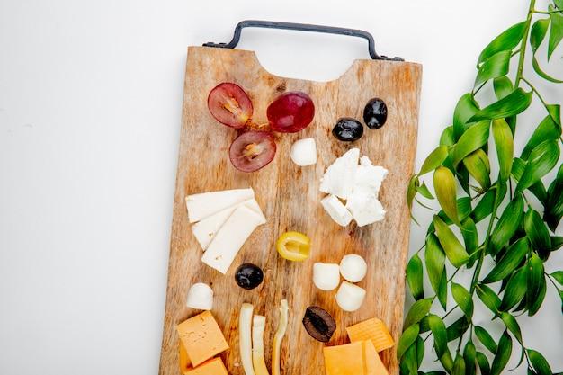 Вид сверху различных видов сыра с кусочками винограда и оливок на разделочной доске на белом украшенный листьями с копией пространства