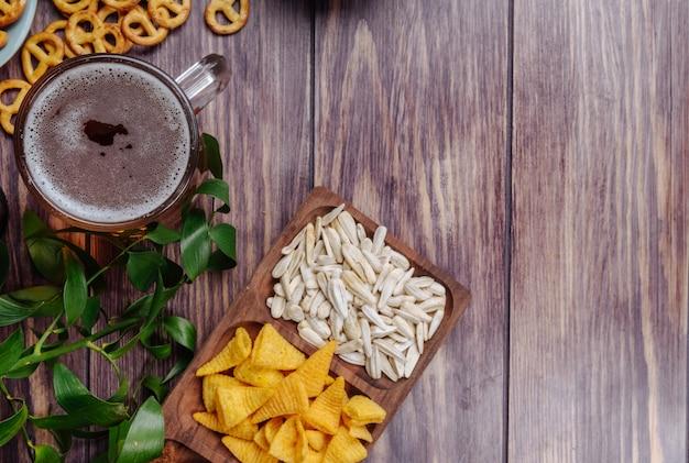 Вид сверху разнообразных пивных закусок из семян подсолнечника и мини-кренделек с кружкой пива на деревенском с копией пространства