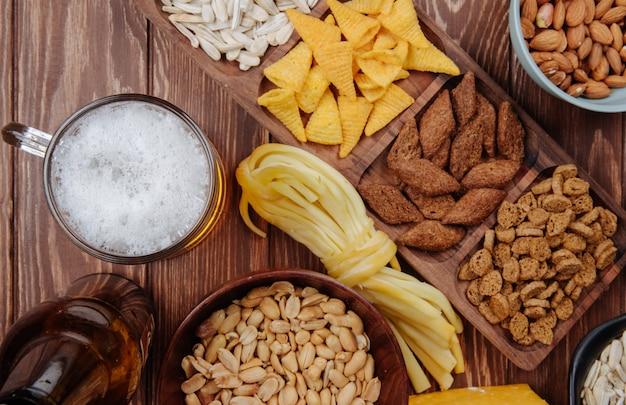 Вид сверху разнообразных соленых пивных закусок с кружкой пива на деревенском дереве