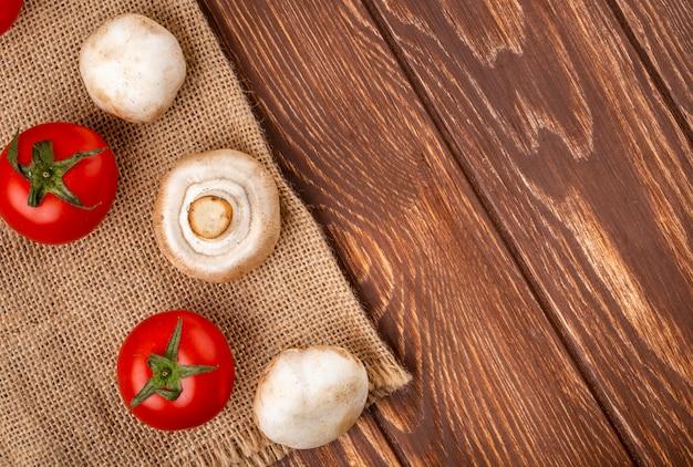 木製の背景に荒布を着た新鮮なキノコシャンピニオンとフレッシュトマトの側面図