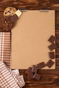 木製の背景にダークチョコレートの部分とオートミールクッキーのスケッチブックのトップビュー