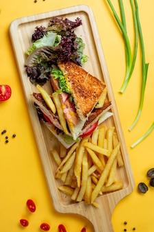 サイドの緑とフライドポテトのクラブサンドイッチ