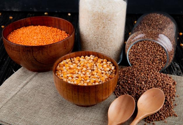 Гречневая крупа спереди разбросана из банки с кукурузной чечевицей и рисом на мешковине