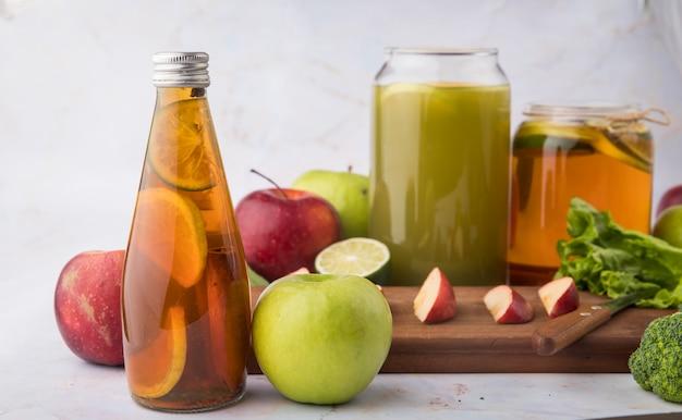 ライムの新鮮なリンゴジュースのブロッコリーレタスの葉の赤と緑のリンゴのシナモンスライスと側面図レモンティー