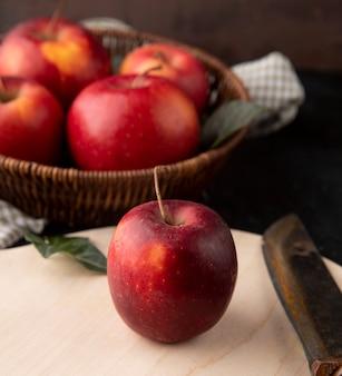 Вид сбоку красные яблоки в корзине с яблоком и ножом на доске