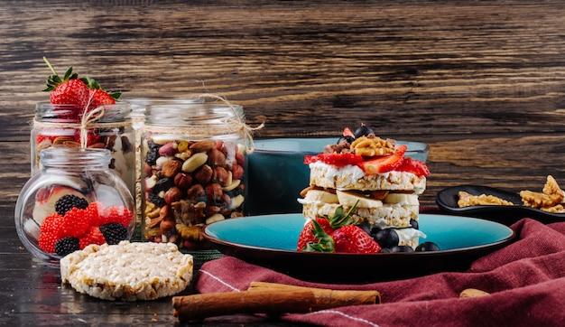 Вид сбоку вкусные хрустящие хлебцы со спелой черникой клубникой и орехами со сметаной на керамической тарелке