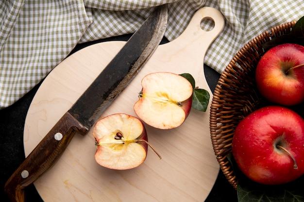 Вид сверху красные яблоки в корзине с разрезанным пополам яблоком и ножом на доске
