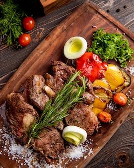 Жареное мясо подается с овощами гриль, луком и веточкой розмарина