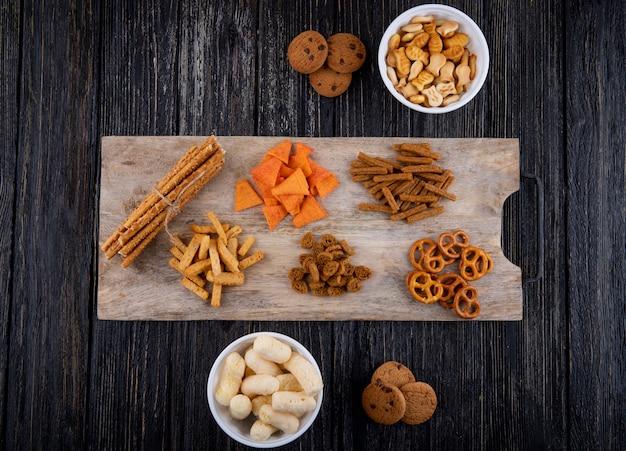 Вид сверху закуски кукурузные палочки мини-брезель в твердом виде, шоколадное печенье, паприка, чипсы и сухарики на черном деревянном фоне