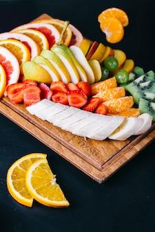 Фруктовый салат с бананами, клубникой, мандаринами, апельсинами и грушами