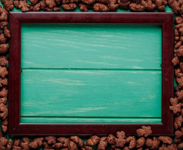 緑の木製の背景にコピースペースを持つ空の図枠の周りに配置されたカリカリチョコレートコーンフレークの平面図