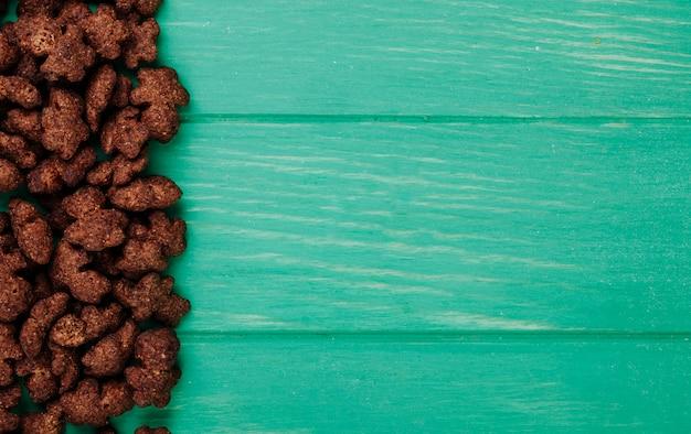 コピースペースを持つ緑の木製の背景にカリカリチョコレートコーンフレークのトップビュー