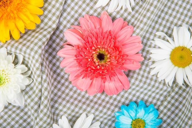 チェック柄のファブリックの背景にデイジーの花とカラフルなガーベラの花のトップビュー