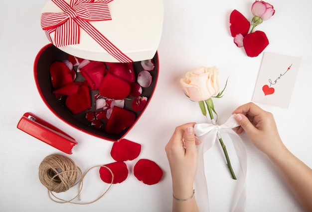 赤いバラの花びらの赤い色のホッチキスロープと白い背景の上のリボンで白いバラを結ぶ女性の手で満たされたハート型のギフトボックスの平面図
