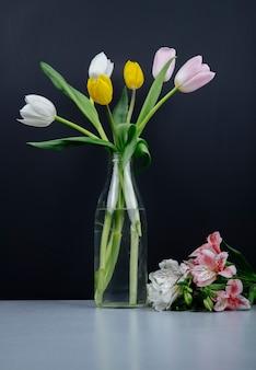 ガラス瓶の中の色とりどりのチューリップの花と黒の背景でテーブルの上に横たわるピンクのアルストロメリアの花の花束の側面図