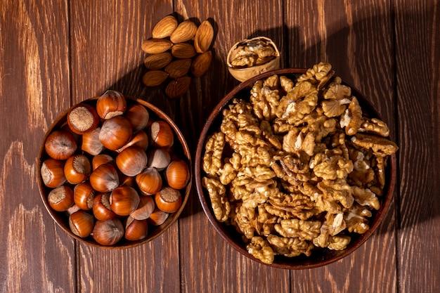 Миска сверху с орехами в скорлупе с миской грецких орехов и миндаля на столе