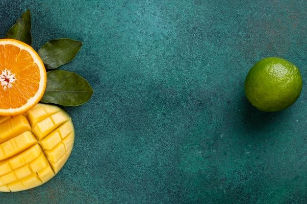 緑のテーブルに半分オレンジとバナナとマンゴーをスライスしたコピースペースを表示します。