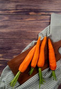 Вид сверху моркови на разделочную доску на ткани и деревянный фон с копией пространства
