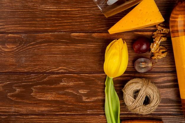 コピースペースを持つ花で飾られた木製の背景にチェダーチーズとブドウの部分とひものクルミのクローズアップビュー