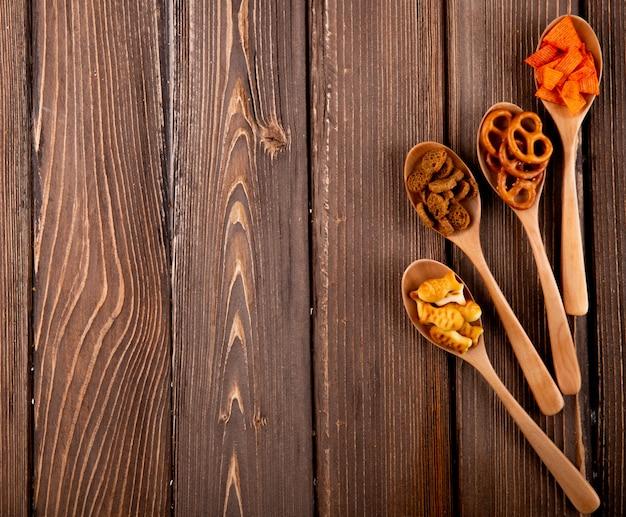 Вид сверху закуски в твердом виде, мини брезель, паприка, чипсы, рыбные крекеры справа с копией пространства на деревянном фоне