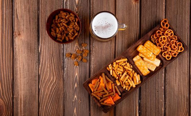 Вид сверху закуски к пиву, твердый цыпленок, мини-чипсы брезель и соленые крекеры с кружкой пива на деревянном фоне