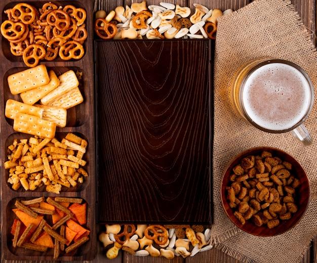 Вид сверху закуски к пиву в твердом виде, мини-брезель, соленые крекеры, рыбные крекеры, чипсы и белые семечки с копией пространства на деревянном фоне