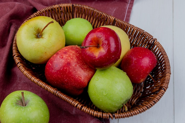 Вид сбоку яблок в корзине на ткани бордо и деревянные