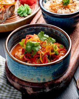 Вид сбоку жареных креветок с овощами и острым соусом в миске на деревенской поверхности
