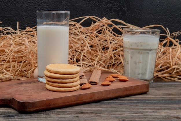 木製の表面と黒い壁にまな板の上のミルクとクッキーアーモンドのガラスの側面図