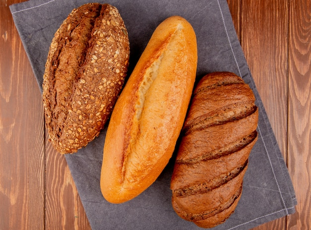Вид сверху хлеба как вьетнамский и черный отобранный багет и черный хлеб на серой ткани и деревянный стол
